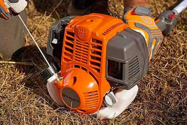 Husqvarna 324L four stroke gas string trimmer on ground